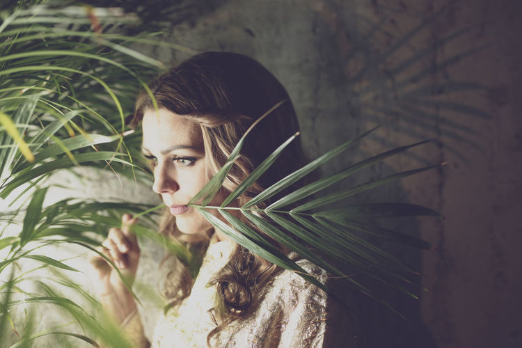 Woman with plant against wall