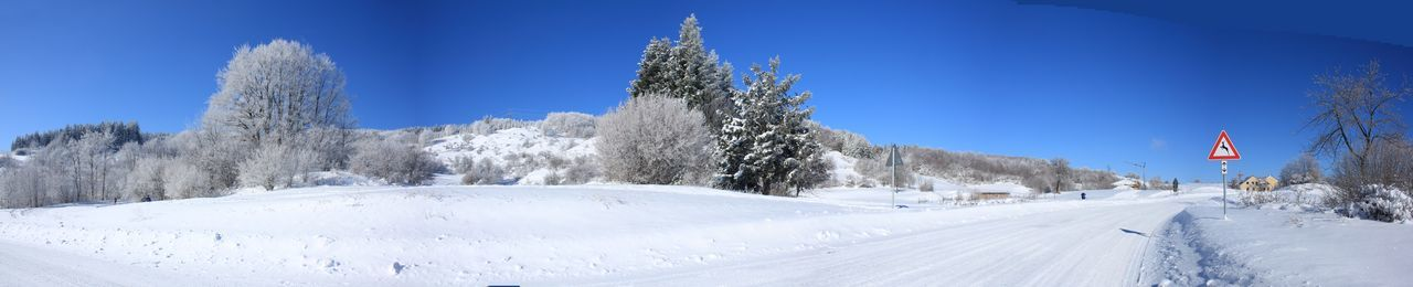 Panoramic view of empty road amidst snowcapped field during winter