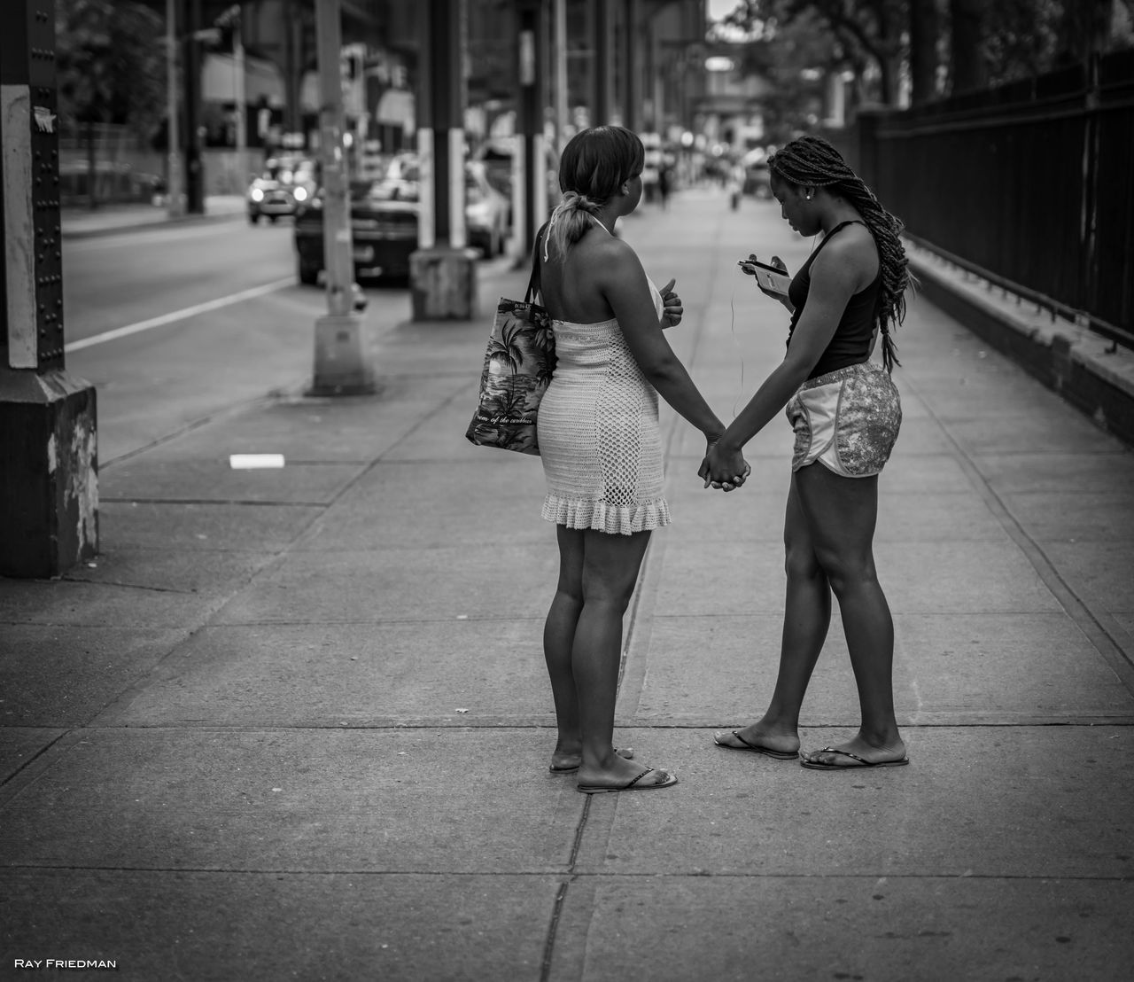 two people, real people, togetherness, full length, leisure activity, rear view, friendship, outdoors, casual clothing, lifestyles, women, young women, day, young adult, standing, bonding, city, adult, adults only, people