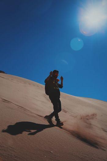 Full Length Of Man Walking On Sand Dune In Desert During Sunny Day