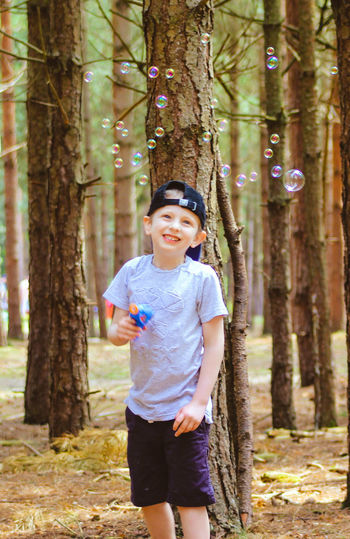 Smiling One Boy Only Children Only Forest Childhood Child Happiness Boys Tree One Person Males  Cheerful Tree Trunk People Nature Portrait Casual Clothing Looking At Camera WoodLand Outdoors Bubbles Bubble Bubbles... Bubbles...Bubbles.... Premium Collection