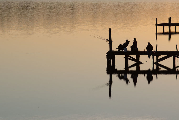 Quiet evening at the lake Water Reflection Waterfront Silhouette Real People Sunset Lake Nature Sky Tranquility Beauty In Nature Scenics - Nature Men Tranquil Scene Fisherman Fishing People Outdoors Reflections In The Water