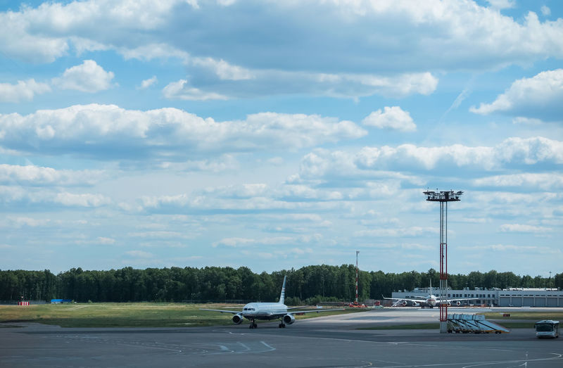 Runway and aircraft at the airport Cloud - Sky Transportation Mode Of Transportation Sky Motor Vehicle Car Land Vehicle Road Street Nature Day No People City Tree Outdoors Travel Plant Street Light Air Vehicle Motion