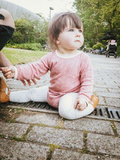 Cute girl sitting on footpath
