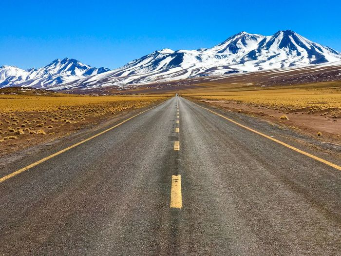 Empty road leading towards snowcapped mountains against clear sky