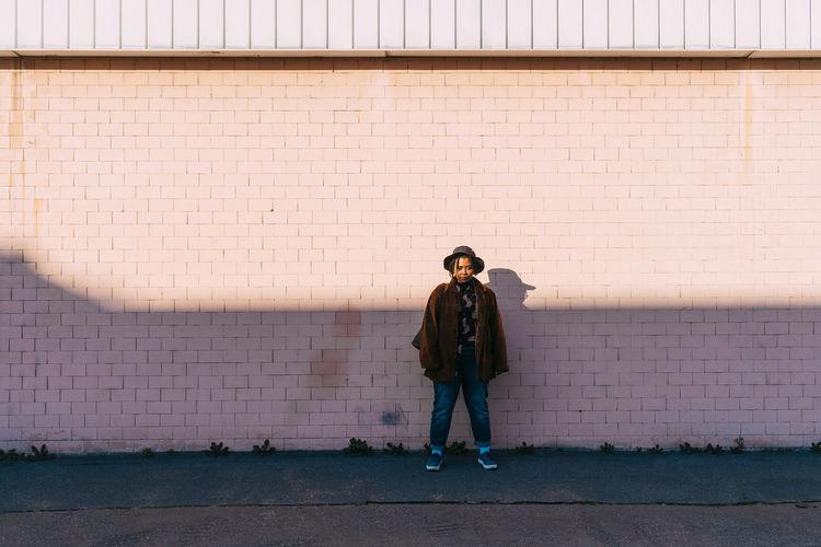 Full length of man standing on sidewalk against wall