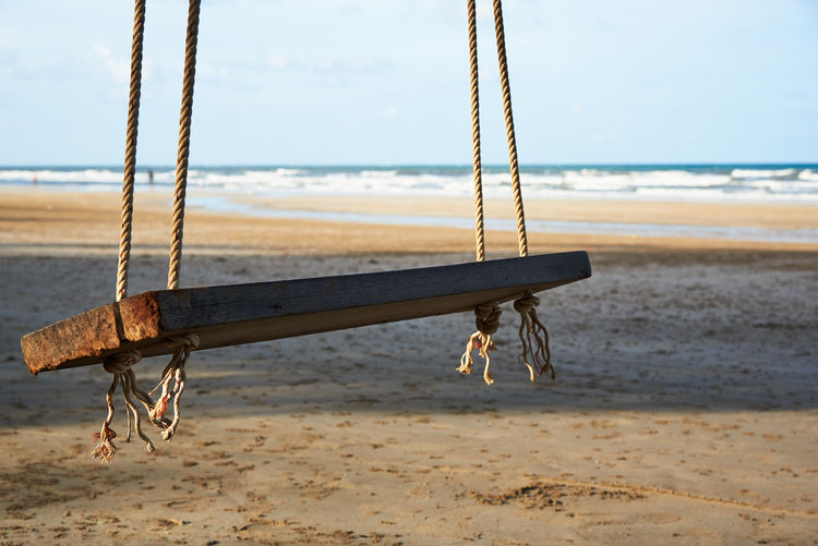 A wooden swing hanging on the tree on the beautiful blue sky and clouds background. Morning sunlight and shadow on the beach. Swing Beach Wooden Sea Tree Tropical Thailand Summer Beautiful Sky Water Island Vacation Sand Travel Paradise Landscape Nature Blue Background Ocean Holiday Sun Outdoor Tourism Relax Coast Rope Relaxation White Wood View Wave ASIA Exotic Nobody Sunny Shore Hanging Cloud