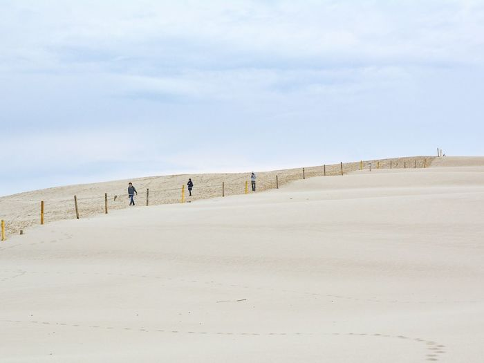 Low angle view of people walking on sand dune at desert