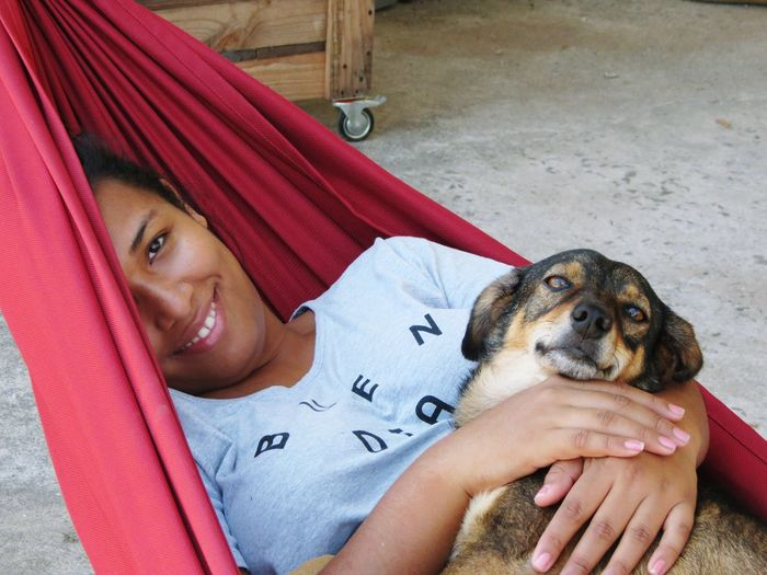 Portrait Of Woman And Dog Relaxing In Hammock