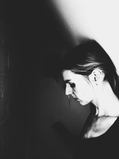 Side View Of Sad Young Woman Standing By Wall