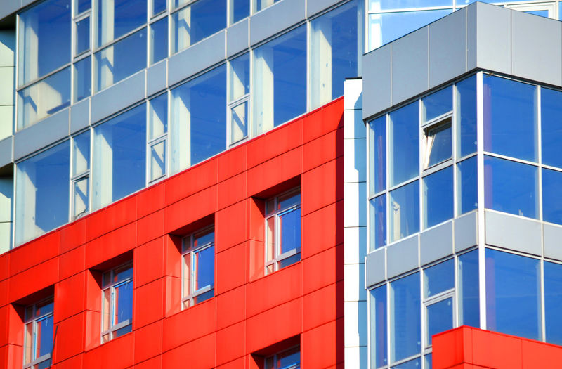 Part of the facade of a modern building with red walls, square windows, the blue mirrored glass.