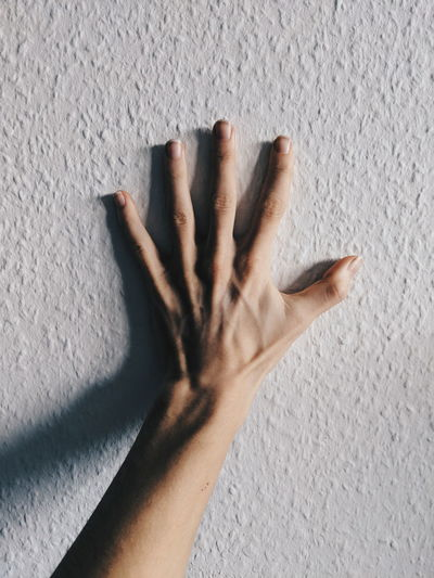Cropped hand touching white wall