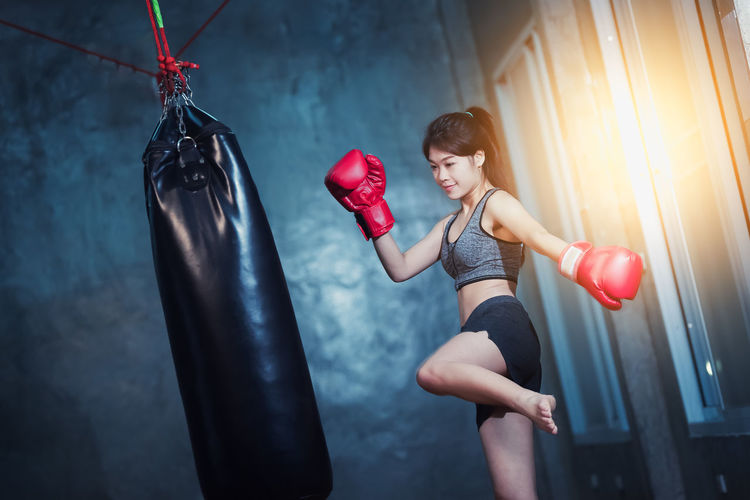 Young woman punching boxing bag at gym