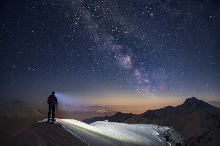 Man standing on mountain against sky at night