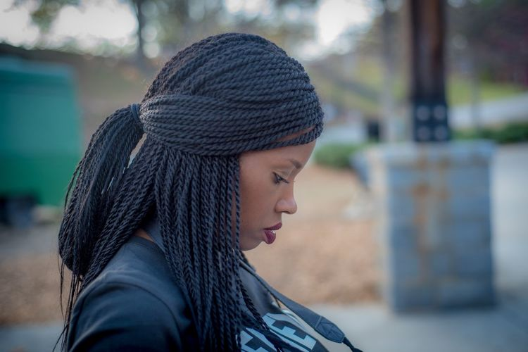 Woman with braids looking down while sitting in park. Braids African-american EyeEm Selects Headshot One Person Focus On Foreground Real People Young Adult Lifestyles Side View Portrait Hairstyle Hair Black Hair Close-up Day Outdoors Young Women Leisure Activity Looking Profile View