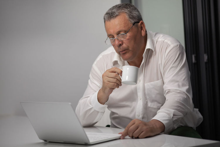 Serious mature businessman drinking coffee while looking at laptop in office