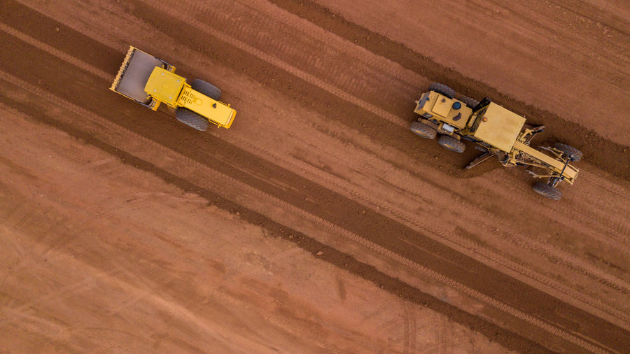 Aerial view yellow excavator building a highway, road grader heavy earth moving, bulldozer working