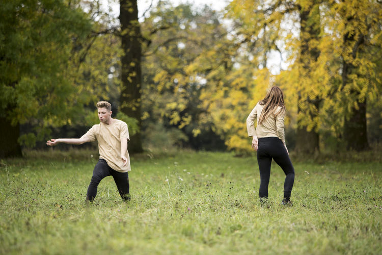 Young Couple Dancing On Grassy Field At Park