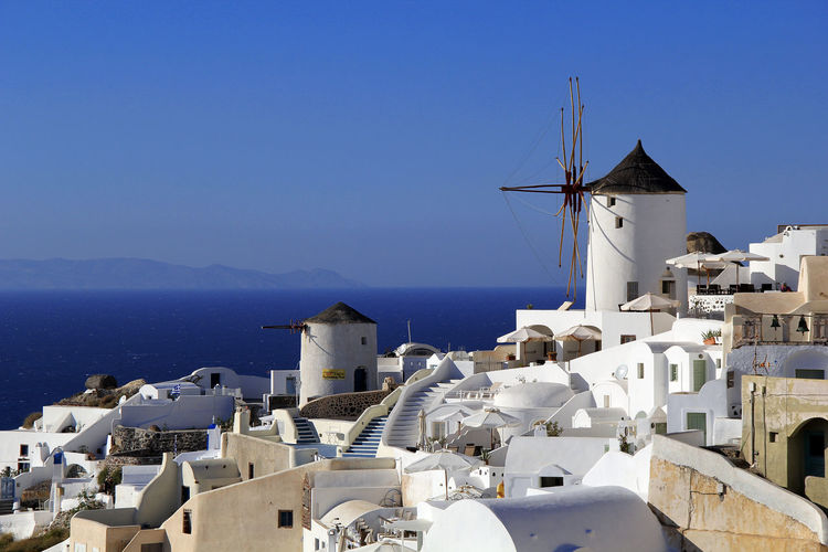 Traditional windmills amidst buildings on mountain by sea against clear blue sky