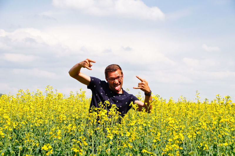Portrait of happy mid adult man gesturing on oilseed rape field against cloudy sky