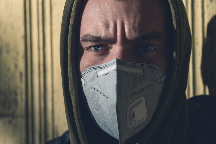 Close-up portrait of young man covering face