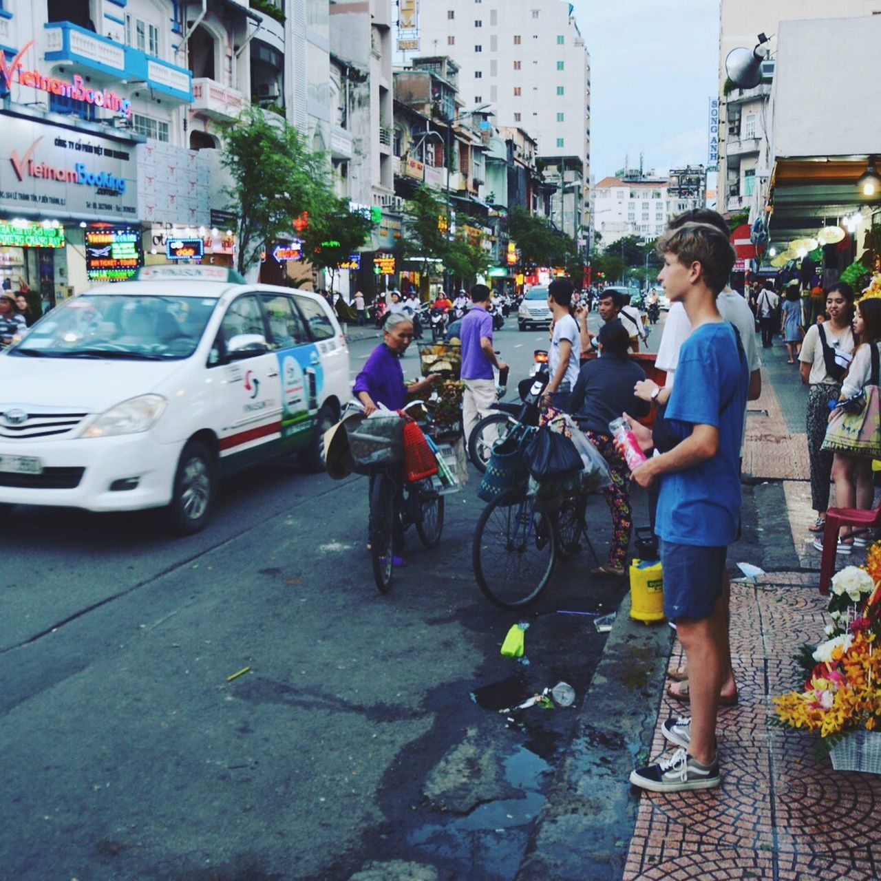 land vehicle, city, building exterior, mode of transport, transportation, bicycle, street, built structure, real people, car, architecture, city life, outdoors, day, full length, holding, lifestyles, men, large group of people, standing, women, young adult, adult, people, adults only