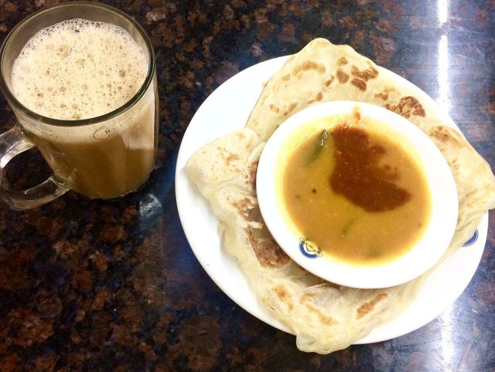 eating malaysian food 'roti canai' with drinks 'teh tarik' in evening Culture Food Malaysian Food And Drink Food And Drink Drink Table Refreshment Plate Still Life Freshness Healthy Eating Serving Size Ready-to-eat Close-up Drinking Glass High Angle View Food Indoors