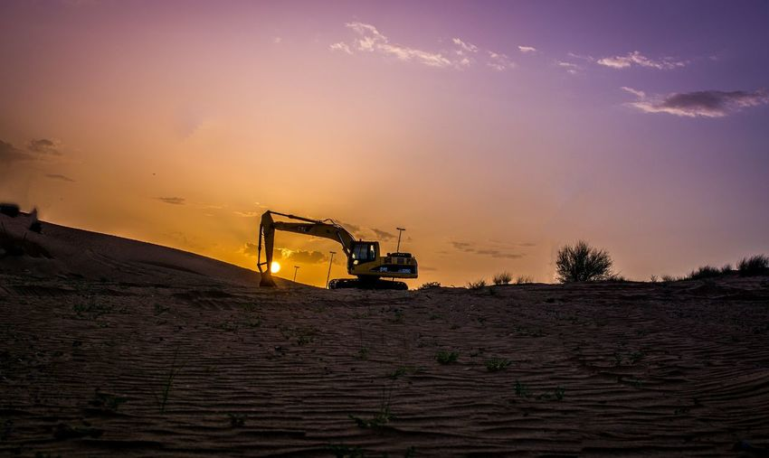 Excavator on sandy field against sky during sunset
