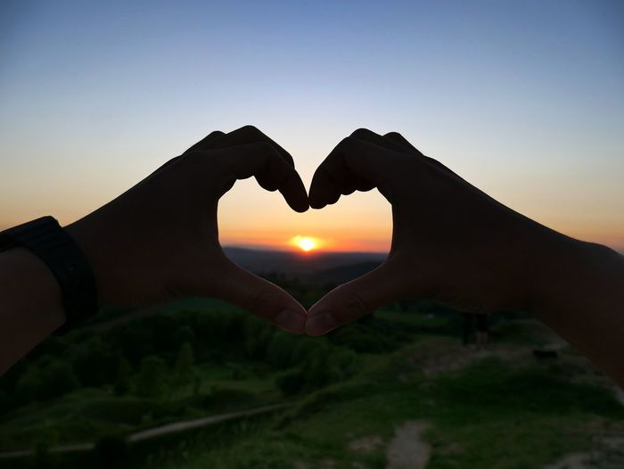 Close-up of hand holding heart shape against sky during sunset
