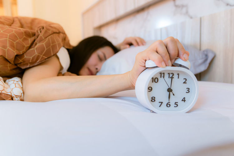 Close-up of woman holding alarm clock while lying on bed at home