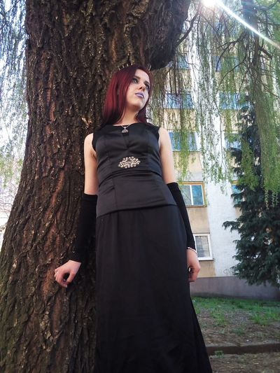 Portrait of smiling young woman standing by tree in forest