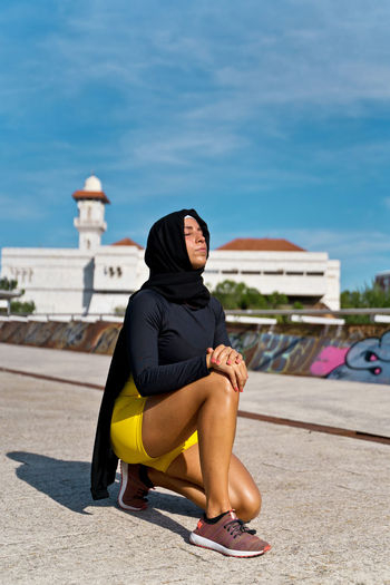 Full length of woman sitting against sky in city