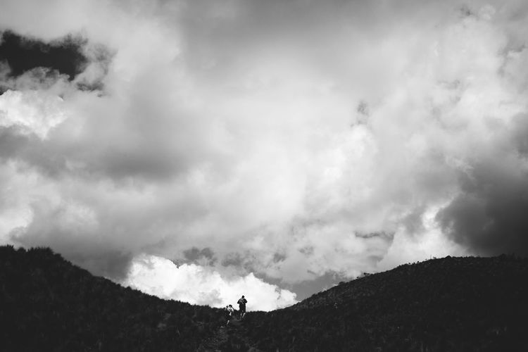 Mid distance view of people hiking on mountain against cloudy sky