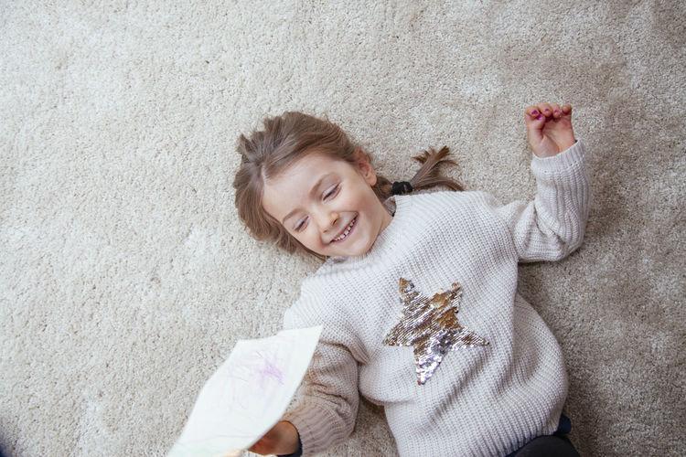 High angle portrait of smiling girl lying on floor
