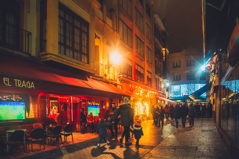 Building Exterior Illuminated Group Of People City Night Architecture Built Structure Real People Street Men Large Group Of People City Life Crowd Women Walking Text Lifestyles Building Adult Outdoors The Way Forward Walking Around The City  Christmas Lights Leisure Activity Leisure