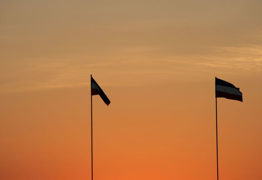 2 Flags Dusk Flag Flags Flags In The Wind  No People Orange Orange Sky Outdoors Sunset Whispy Clouds