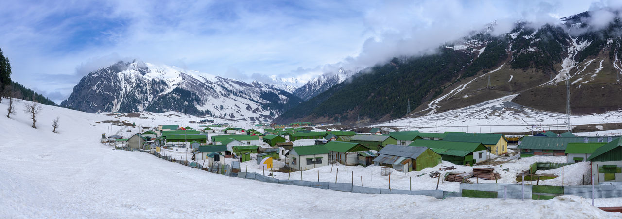 Panoramic view of buildings and snowcapped mountains against sky