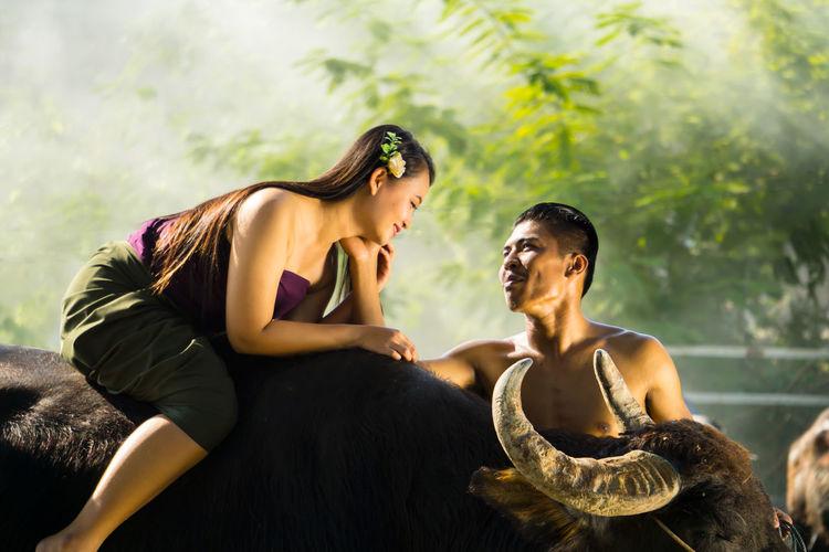 Loving boyfriend touching girlfriend sitting on buffalo