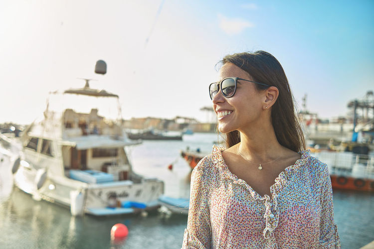 Portrait of a smiling young woman in boat against sky