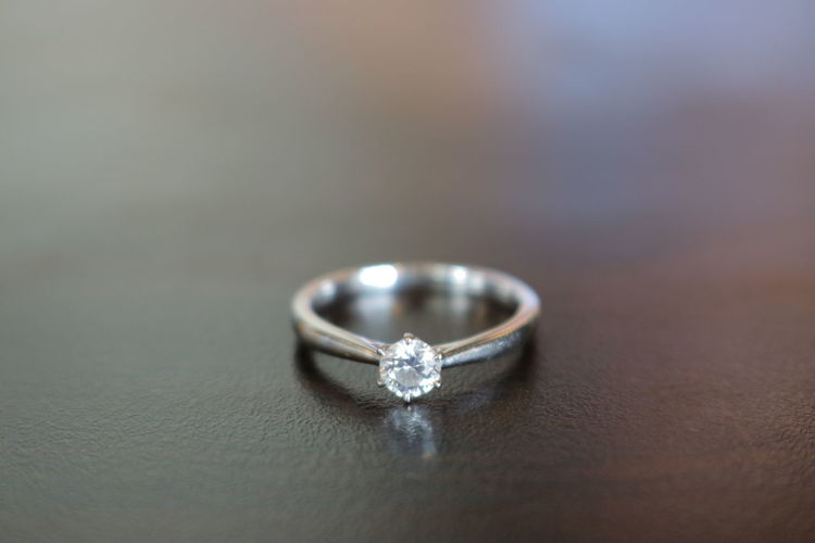Asian woman holding a white gold engagement ring, pure gold, Philippines Jewelry Diamond - Gemstone Wealth Ring Luxury Close-up Diamond Ring Wedding Ring Engagement Ring Precious Gem Silver Colored Asian  Pure Gold Ring On The Table Ring On Finger Ring On Hand Close Up Ring Ring Close Up