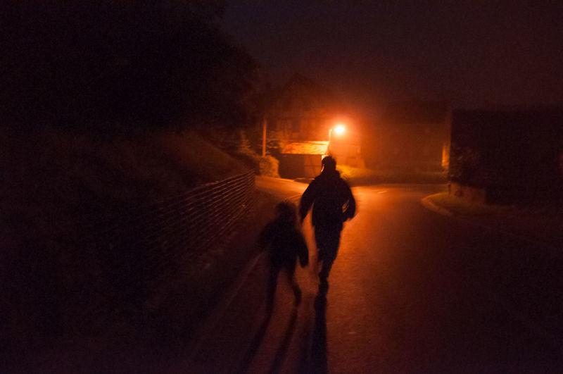 Silhouette of people walking on street at night