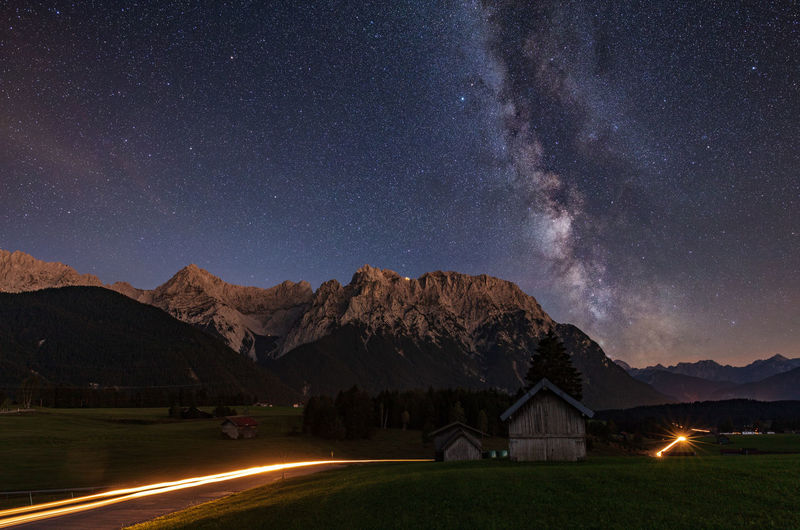 Light trails on road with mountains in background against star field