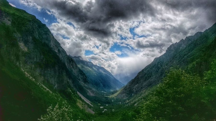 Scenic view of valley and mountains against cloudy sky