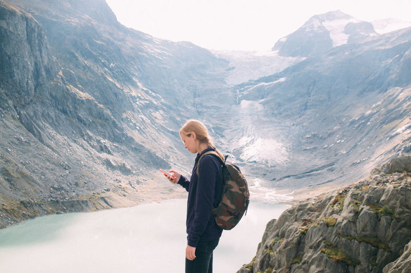 Young woman looking at phone with mountain lake seen below