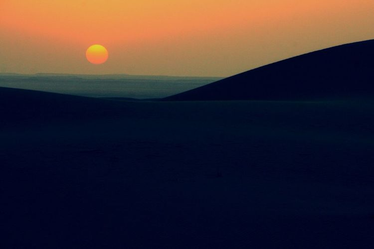Scenic view of silhouette land against sky during sunset