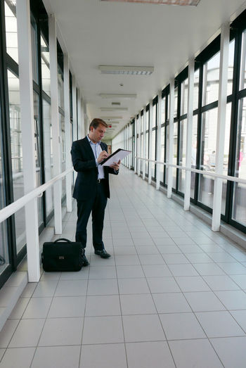 Businessman Standing With Documents At Office Corridor