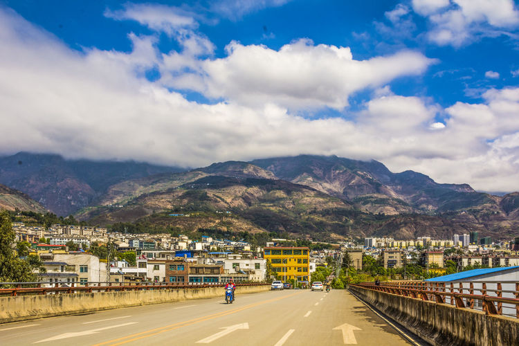 Road by mountains against sky in city