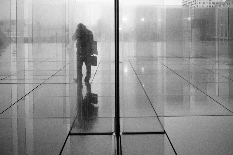 Reflection of woman on tiled floor