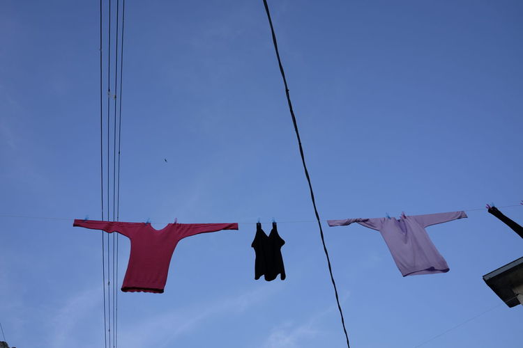 Low Angle View Of Clothes Drying On Power Lines Against Sky