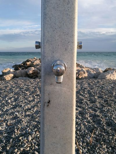 Close-up of metal container on beach against sky